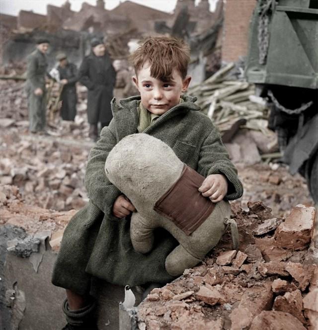 カラー化写真 ぬいぐるみを抱く孤児の少年